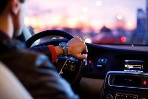 גבר נוהג במכונית עם שעון יוקרתי